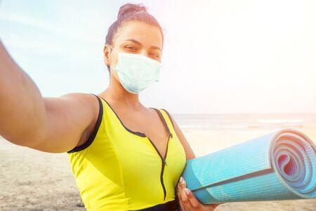 indian woman meditating on sea beach outdoor in medical mask Reklamní fotografie