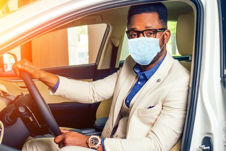 Handsome man in medical mask is standing near his new car and smiling Reklamní fotografie