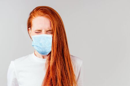 fingers crossed wishing the best in studio gray background redhair ginger woman feeling unhappy and wearing medical mask Reklamní fotografie