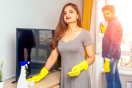 Young couple indian moving in new home, cleaning and unpacking big window with stylish yellow curtain background