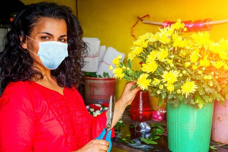 cheerful young woman in mask brunette florist selling flowers in a flower shop