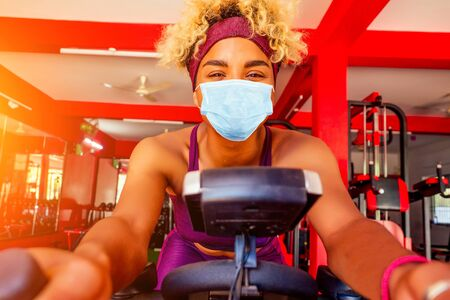 african american woman in mask cardio slimming aerobics training on bicycle Reklamní fotografie