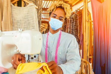 african american woman in medical mask standing and arms crossed near her sewing machine in tropical workshop in Bali