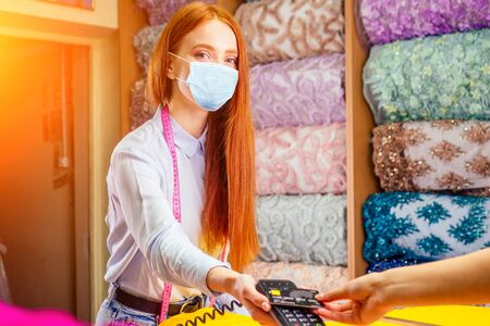 redhaired ginger cashier woman in fabric shop giving bill transaction machine to female customer