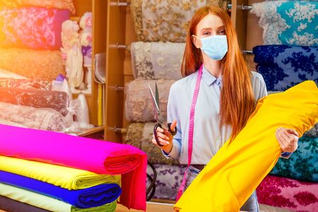 redhaired ginger dressmaker woman cropping cutting textile in shop behind her background stock with bright sequins sparkling fabric