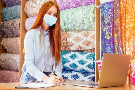 redhaired ginger business woman in mask working at textile shop.Redhead salewoman in storage update cotton and lace fabric capsule wardrobe