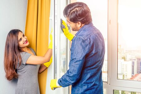 Smiling young indian couple cleaning windows cleaning and unpacking , stylish yellow curtain background