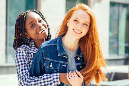 cheerful afro and european women laughing and looking at camera at summer downtown city