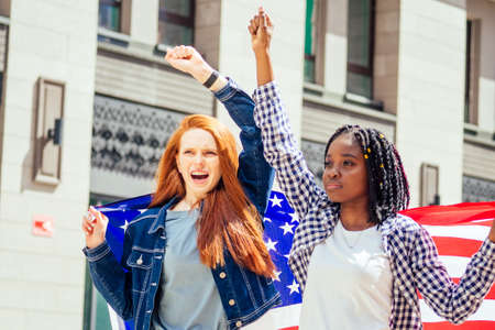 lesbian redhaired ginger woman and her african american wife holding USA flag in downtown street