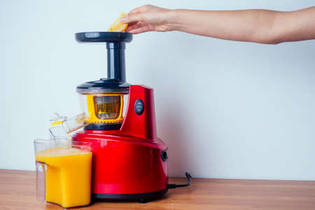 raw food diet concept oranges and juicemachine in white background