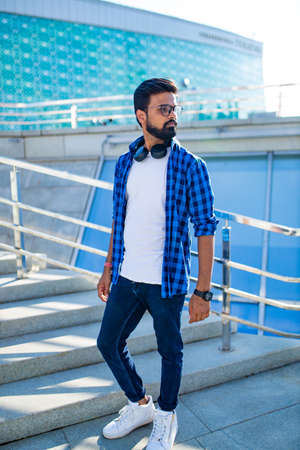handsome bearded brunette arabian man listen musics outdoor street