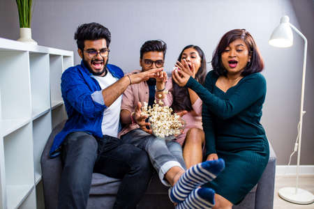four indian friends watching cinema in the night time at home throwing popcorn