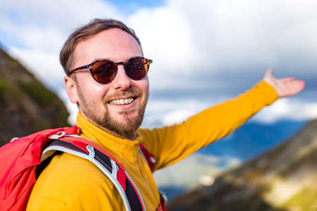 smiling man with braces on mountains