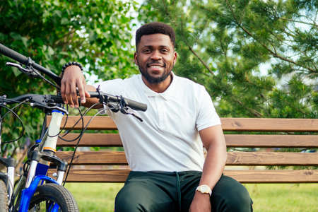 ecology and transportation concept. modern young Afro American businessman cycling to work on bicycle Banco de Imagens