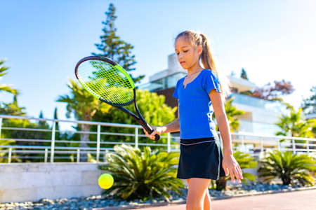 little girk playing tennis in tropical place outdoors Banque d'images