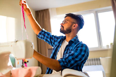 arabian man designer sewing clothes on sewing machine in studio workplace home Banco de Imagens