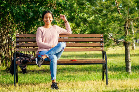 Vietnamese woman in pink sweater sitting on the bench