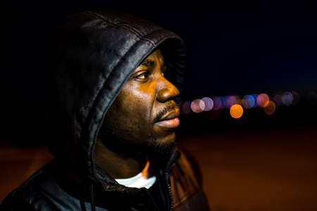 hispanic man in hoodie looking away in twilight downtown streets in park