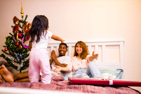 mixed race family awaking in bedroom happy little girl dancing and jumping on the bed