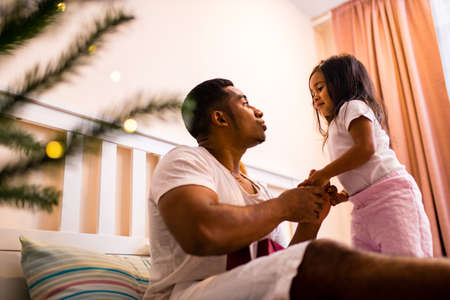 happy mixed race father and cheerful beautiful daughter decorating interior in livingroom