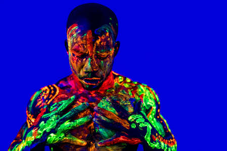 afro american man with UV body art posing in studio Standard-Bild