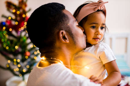happy mixed race dad and beautiful child in the merry x-mas morning in bedroom