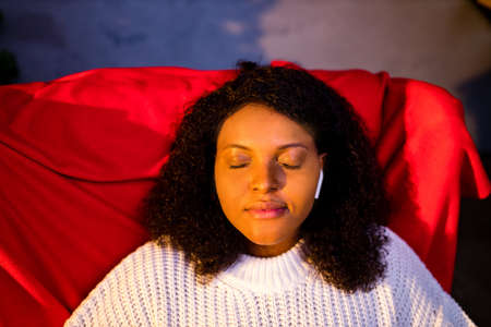 Serene young woman closed eyes relaxing leaned on couch modern wireless headphones in an ear pods Stock Photo