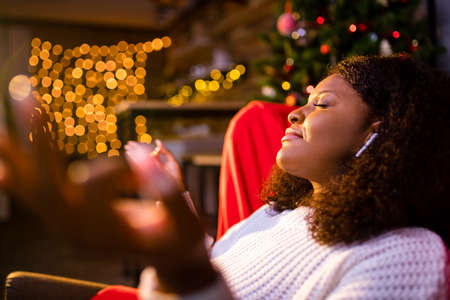 Serene young woman closed eyes relaxing leaned on couch modern wireless headphones in an ear pods