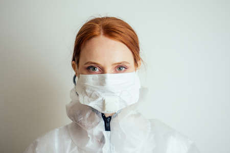 virologist woman in chemical protection mask ,glasses and gloves holding potential vaccine at the lab