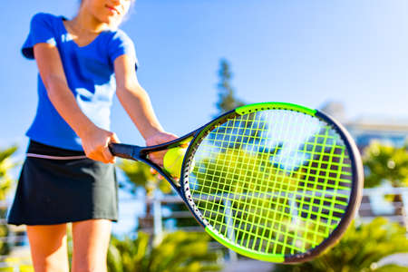 Portrait of a young girl with a tennis racket and ball outdoors tropical background