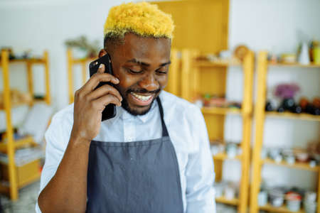 afro male potter talking on the phone in his studio 写真素材