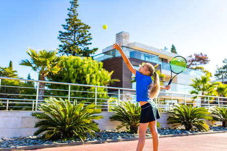 little girk playing tennis in tropical place outdoors