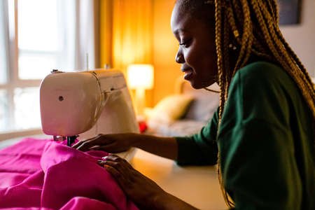 afro american stylist sewing all night long and feeking bad Фото со стока