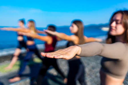 group of young females practicing yoga on the seaside