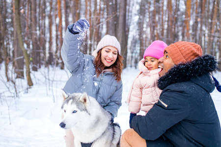 afro man with his caucasian wife having fun with a beautiful daughter playing husky in snowy park 免版税图像