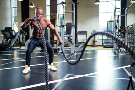 young african muscular athlete working out with ropes in gym