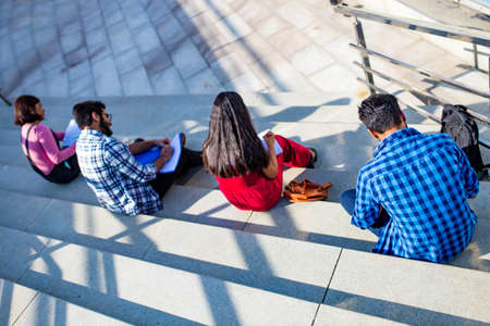 indian students keeping distance and do home work outdoors