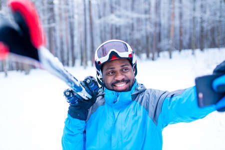 afro american man in blue jacket run ski outdoors in freeze forest 免版税图像