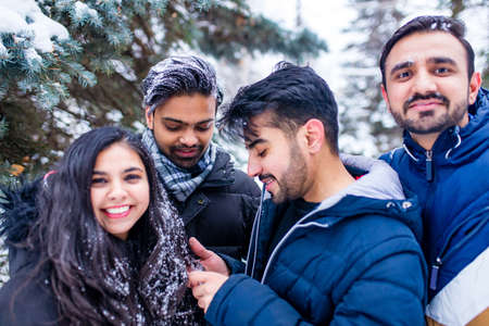 group of four indian having fun playing in snow outdoors spending Chrisymas holidays