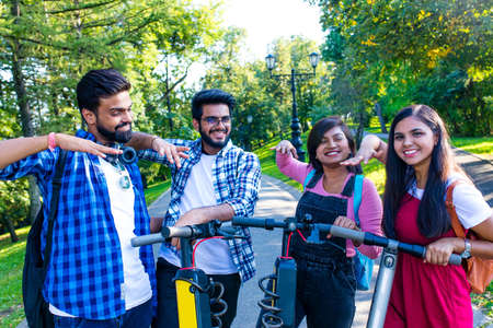 modern indian friends ride on scooter in park in India