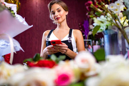 Female florist standing at her flower shop counter using mobile phone delivery