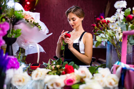 graceful blonde woman in apron selling a flowers in her store own