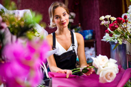 young woman flower store manager standing at workplace and smiling reopening shop sale 免版税图像