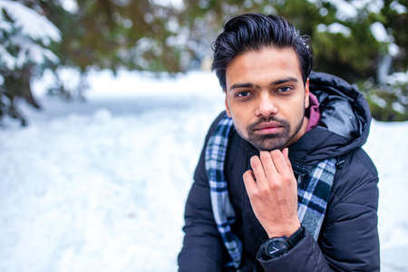 indian man enjoying snowflakes falling from upwards in forest