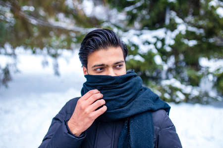 indian man enjoying snowflakes falling from upwards in forest wrapped nose and mouth with the scarf becouse he he forgot the medical mask