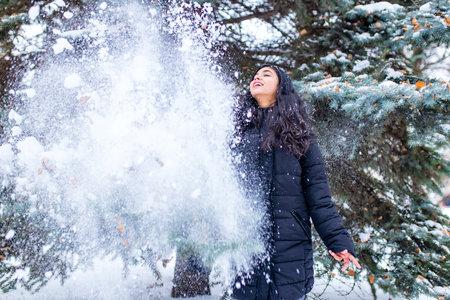happy indian beautiful brunette woman in snow in forest 免版税图像