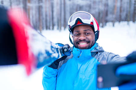 afro american man in blue jacket run ski outdoors in freeze forest holding a phone on hands
