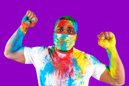 latin brazilian male in white cotton t-shirt with colorful paint of face laughing studio