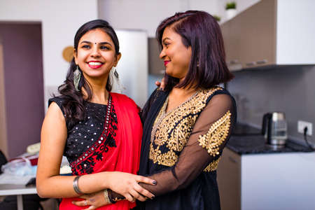 two indian women with bindi on the forehead hugging in living room