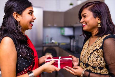 Deepavali or bhai Dooj festival - Indian young friends celebrating Diwali or Rakshabandhan Celebration at living room in home 版權商用圖片